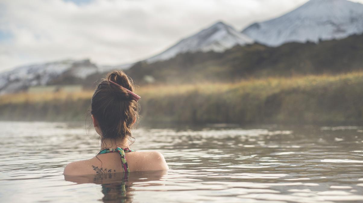 Girl-in-a-hot-spring-in-Iceland-Landmannalaugar-iStock-gorodisskij-www.istockphoto
