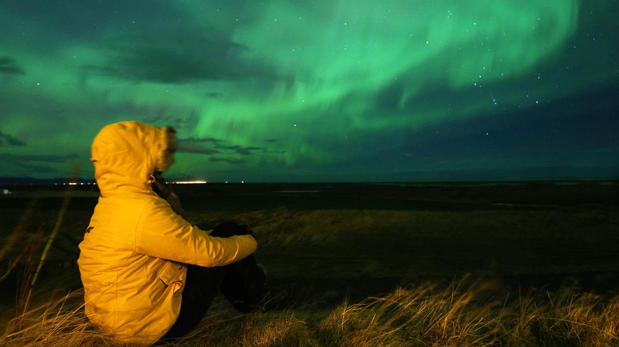Traveller-Looking-Admiring-Northern-Lights-During-Aurora-Storm-iStock-JurgaR-www.istockphoto