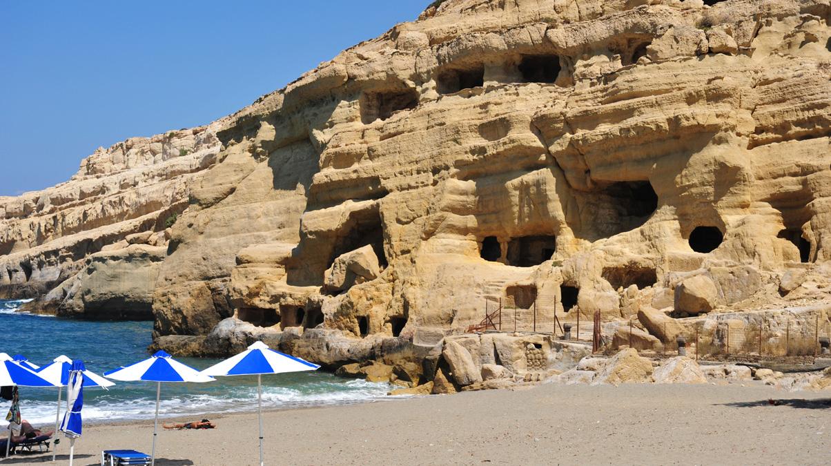 Beach-and-sandstone-cliffs-at-Matala,-Crete,-Greece-iStock-clubfoto-www.istockphoto